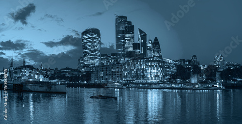 Panorama of the modern skyline on Thames river at twilight blue hour - London, United Kingdom -                Night view of the downtown City of London