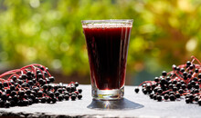 A Glass Of Black Elder Syrup With Fresh Elderberries Outdoors