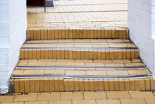 Steps With Rubber Non-slip Strips On The Arch Staircase At The Entrance To The White Brick Building Close-up, Nobody.