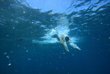 Underwater Photo Of Man Diving Into The Refreshing Clear Blue Ocean