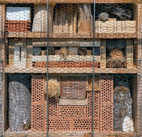 Sonniges Insektenhotel mit vielen verschiedenen Materialien hinter Maschendraht
