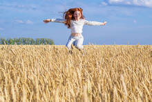 A Little Young Girl With Red Hair Flies Over A Golden Wheat Field Against The Blue Sky.