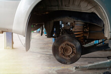 A Car Whose Wheels Were Removed To See The Structure Of The Car's Brakes Were Large Brake Discs, Rusting Iron.