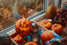 Halloween Cozy Mood Composition On The Windowsill. Lighting Jack-o-lantern, Decorative Pumpkins, Cones, Candles On Wooden Tray And Straw Napkin, Warm Plaid. Hygge Halloween Home Decor. Selective Focus