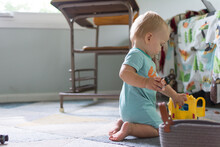 14 Month Old Baby Kneeling On The Ground Playing With School Bus Toy And Figures