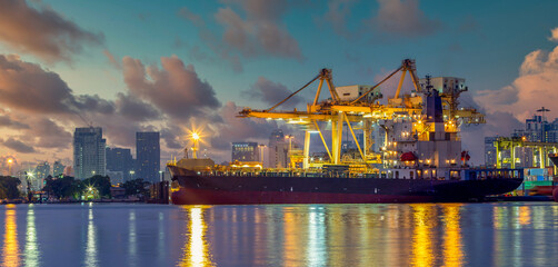Container ship at container terminal at night, Industrial container cargo freight ship with working crane bridge in shipyard for global business industry logistic import export transportation company.