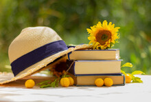 Straw Hat, Sunflower Flower On A Stack Of Books On The Table In The Garden. Rest, Reading, Vacation Concept