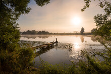 Fishing Bridge For A Boat And A Calm Morning Landscape Surrounded By Greenery At Sunrise With Fog Over The River.