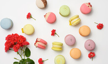 Baked Macarons With Different Flavors And Rosebuds On A White Background, Top View
