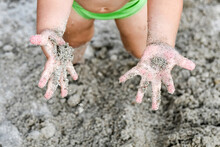 The Child Tries To Remove All The Sand Adhering To His Hands.