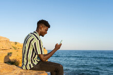 African Male Using Smartphone On Beach Rocks Background.