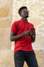 Young Man Using Smart Phone Walking In City In Red Sun Glasses