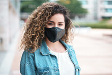 Latin Woman Wearing A Face Mask While Standing Outdoors.