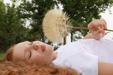 Cute Girl With Beautiful Red Hair Blowing Large Dandelion While Lying On Green Grass In Park. Allergy Free Concept