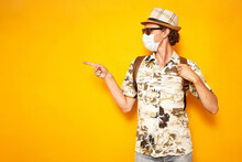 Male Tourist Hawaiian Shirt, Hat, Sunglasses Holds Backpack With His Hand And Points His Finger In Direction Of An Empty Space Of Text Area To Left Yellow Background. Traveling And Covid19 Vaccination