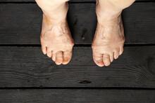 Old Female Feet On Black Wooden Floor