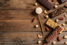 Different Tasty Bars, Nuts And Scoop Of Protein Powder On Wooden Table, Flat Lay. Space For Text