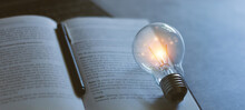Glowing Light Bulb On The Book. Self Learning Or Education Knowledge And Business Studying