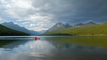 Man Paddling On Bowman Lake In Glacier National Park, A Terrific Place To Go Camping, Hiking, Or Fishing In Montana.