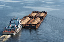 A Tugboat Pushes Barges With Sand On Calm Water, Top View