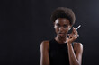 Pretty model african american woman smoking cigarette on black background.