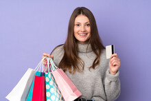 Teenager Caucasian Girl Isolated On Purple Background Holding Shopping Bags And A Credit Card