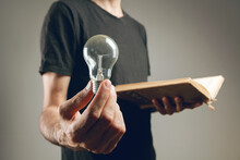 Man Holding An Open Book And A Light Bulb.