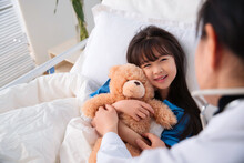 Smiling Girl With Teddy Bear In The Hospital Bed