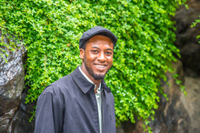 Dressing In A Waterproof Jacket, A Ivy Cap,  A Young Handsome Black Guy Is Standing By Rocks With Green Plants In A Raining Day, Smilingly Looking At You..