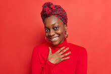 Touched Pleased Dark Skinned Womann Smiles Toothily Keeps Hand On Chest Glad To Hear Compliment Wears Casual Turtleneck Scarf Tied Over Head Earrings Poses Against Vivid Red Background. Monochrome