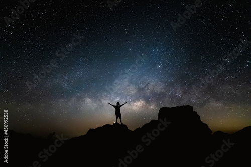 Silhouette of person is standing on the top of the hill next to the Milky Way galaxy with his hands raised to the air.