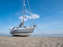 Sailboat Dried Out On Sand Flat At Low Tide Of Waddensea, Island Richel Near Vlieland, Netherlands