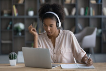 Pensive Millennial African American Female Student In Earphones Study Online On Laptop Handwrite Take Notes. Focused Young Ethnic Woman In Headphones Work Distant On Computer Write Summarize In Pad.