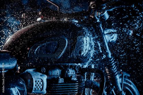 Motocykl w stylu retro przy myciu pod neonowym niebieskim światłem. Mycie wodą detali klasycznego czarnego motocykla. Styl Caferacers. Utrzymanie pojazdów mechanicznych