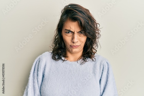 Carta da parati Young hispanic woman wearing casual winter sweater skeptic and nervous, frowning upset because of problem