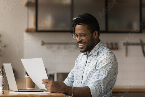Carta da parati Happy African hipster man sit at table in kitchen read great news in document, g