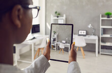 Black Rental Agent Takes Photo Of Apartment Interior Using Smart Tablet. Realtor Video Calling Client, Showing Office Workspace, Giving Tour Around New Home. Over Shoulder Device Display Close Up View
