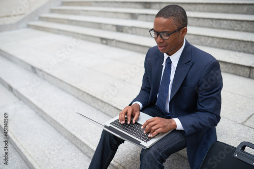 Stampa su Tela Confused frowning businessman sitting on steps outdoors and answering e-mails fr