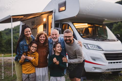 Fotografie, Obraz Multi-generation family looking at camera outdoors at dusk, caravan holiday trip