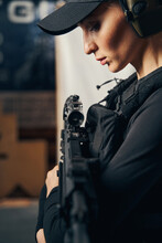 Attractive Female Shooter Pressing The Assault Rifle To Herself