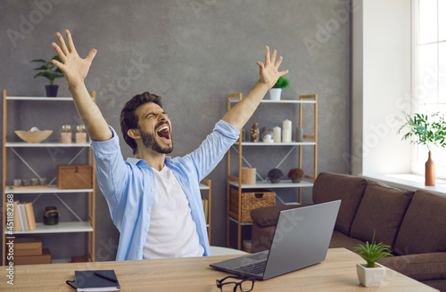 Carta da parati Man sitting at work table with laptop computer feeling excited, raising hands up and screaming