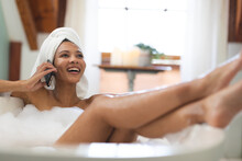 Laughing Mixed Race Woman In Bathroom Having A Bath, Talking On Smartphone With Feet Up