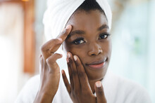 Portrait Of Smiling African American Woman In Bathroom Touching Her Face Before Beauty Treatment