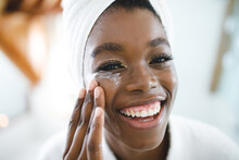 Portrait Of Smiling African American Woman In Bathroom Applying Face Cream For Skin Care