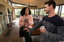 Happy Diverse Couple In Kitchen Sitting On Countertop Drinking Coffee And Talking