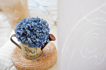Home Decor. A Sprig Of Blue Hydrangea In A Decorative Watering Can For Flowers On A Round Wicker Straw Stand.
