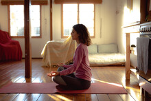 Mixed Race Woman Practicing Yoga, Sitting Meditating In Sunny Living Room