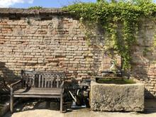 Old Wooden Bench In Front Of Brick Wall In Schloss Hof Garden