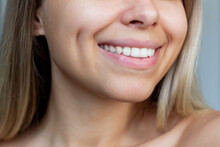 Cropped Shot Of A Face Of A Young Caucasian Smiling Blonde Woman With Dimples On Her Cheeks. Close-up Of A Blonde Girl With Even White Teeth. Dentistry
