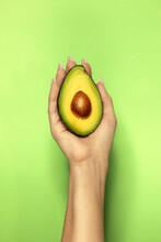 Crop Woman Showing Fresh Avocado Half With Seed
